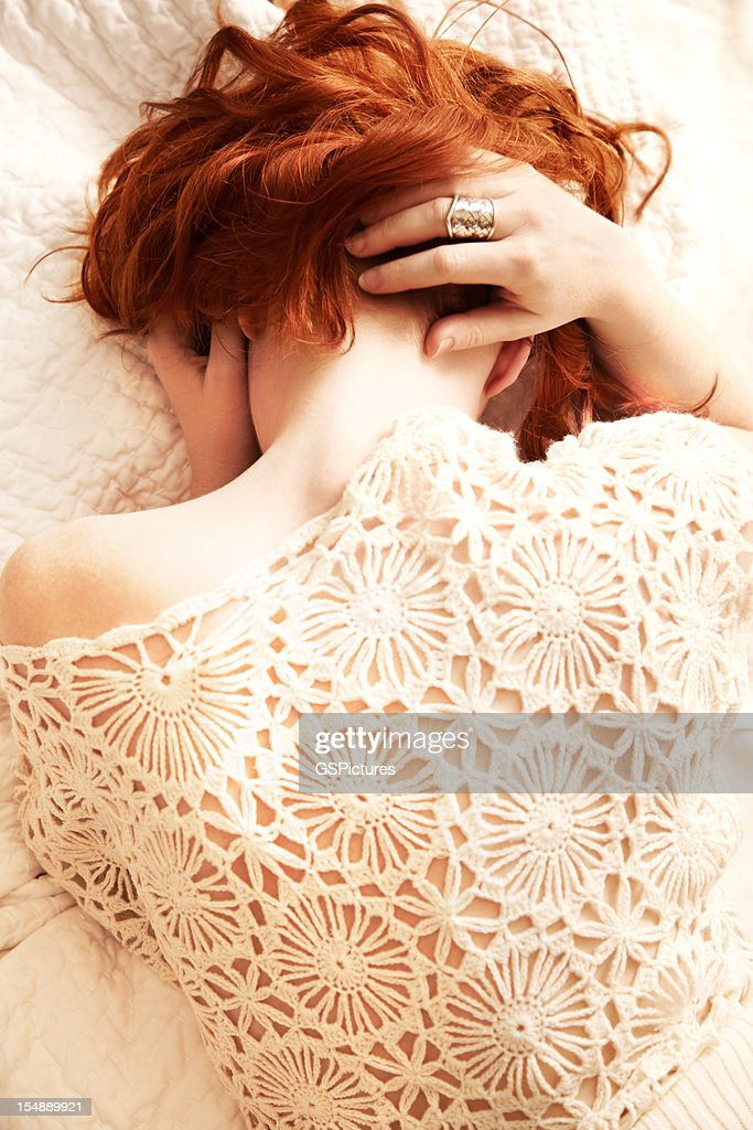 Redhead woman lying in bed with face obscured : Stock Photo
