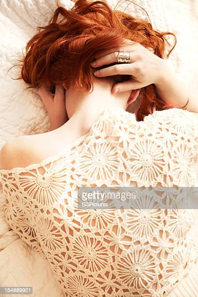 Redhead woman lying in bed with face obscured