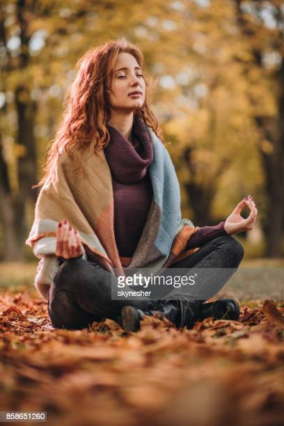 Redhead woman meditating in autumn day at the park.