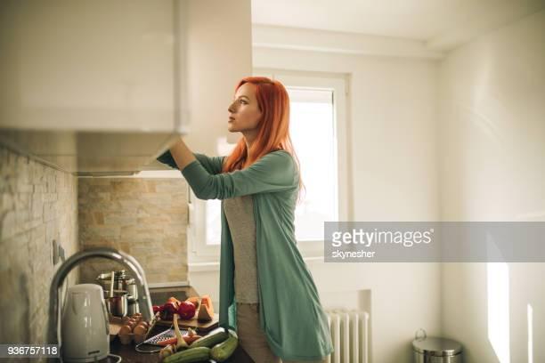 redhead woman searching for something in kitchen cabinet. - armadietto da cucina foto e immagini stock