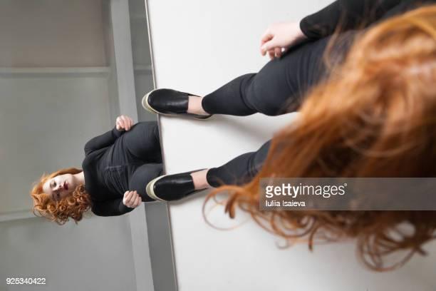 Redhead woman touching reflection