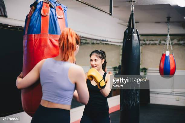 Redhead woman training and female athlete with punching bag at health club