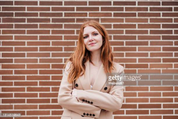 redhead woman with arms crossed staring while standing in front of brick wall - 20 24 years stock pictures, royalty-free photos & images