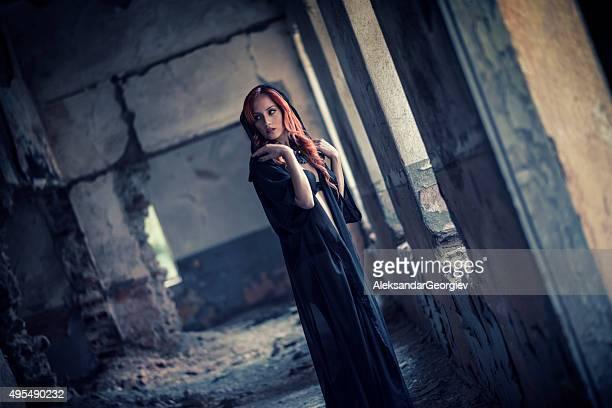 rotes haar-frau mit schwarzem kleid verstecken in alten zerstörten house - menschliche siedlung stock-fotos und bilder