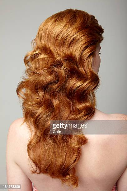 Redhead woman with long curls, rear view.