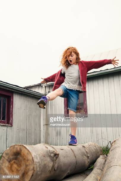 """redhead young girl playing on wood log near barn outdoors. - """"martine doucet"""" or martinedoucet stock pictures, royalty-free photos & images"""