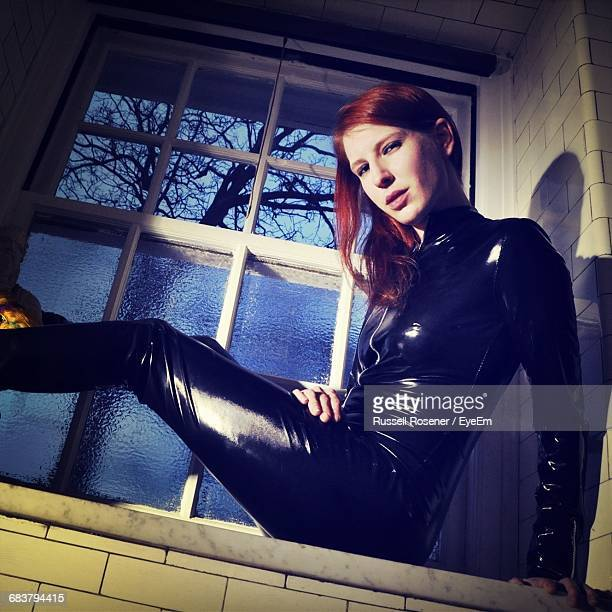 redhead young woman in latex suit - dominatrice photos et images de collection