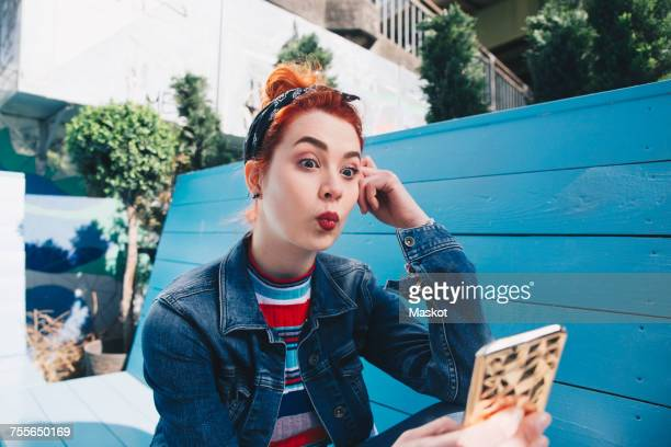 Redhead young woman taking selfie with mobile phone while sitting on bench