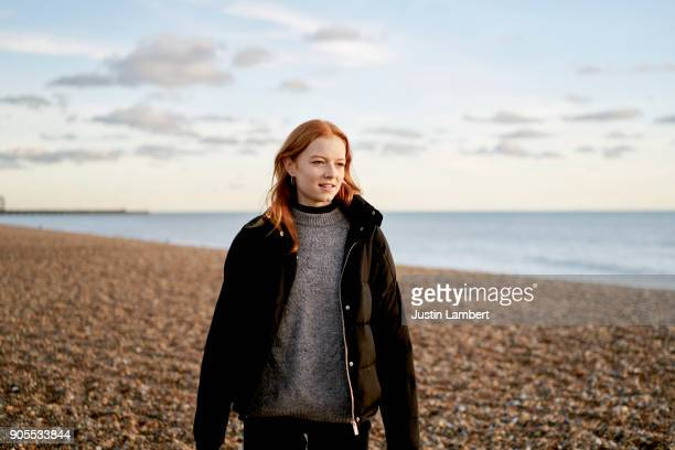 redhead youth walks along beach in winter in puffer jacket - pretty woman stock pictures, royalty-free photos & images
