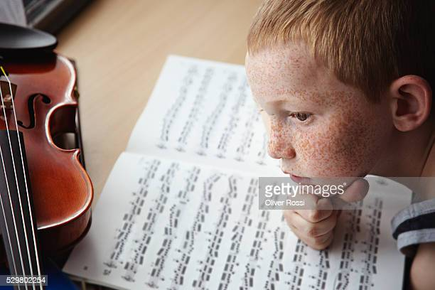 Redheaded boy with violin and sheets of music