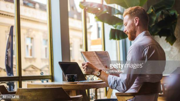 redheaded businessman enjoying the free time for coffee and some news - newspaper stock pictures, royalty-free photos & images