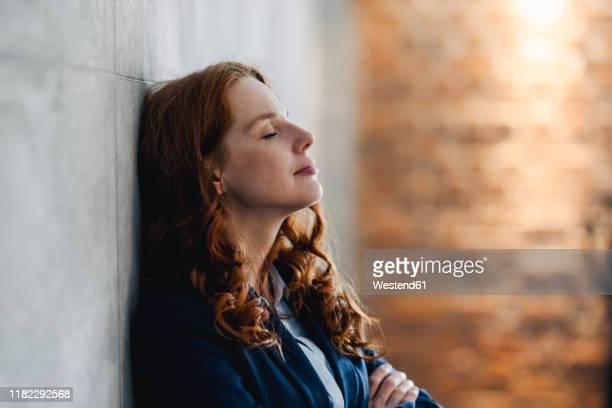 redheaded businesswoman having a break leaning against a wall in office - pause machen stock-fotos und bilder