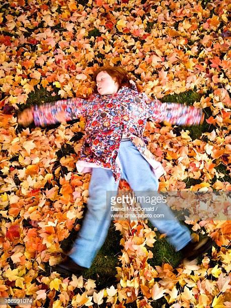 Redheaded girl making an autumnal leaf angel