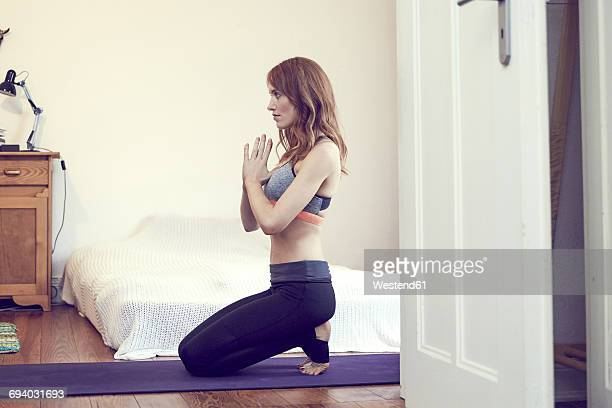 Redheaded woman doing yoga exercise at home