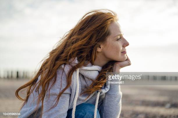 redheaded woman enjoying fresh air at the beach - contemplation stock pictures, royalty-free photos & images