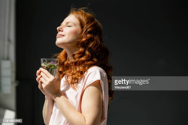 redheaded woman enjoying sunlight - vergnügen stock-fotos und bilder