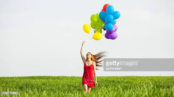 Redheaded woman holding brunch of balloons in field