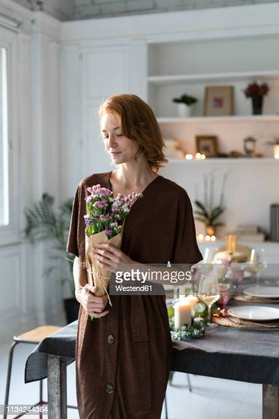 redheaded woman holding bunch of flowers, standing in front of laid table - fragilidad fotografías e imágenes de stock
