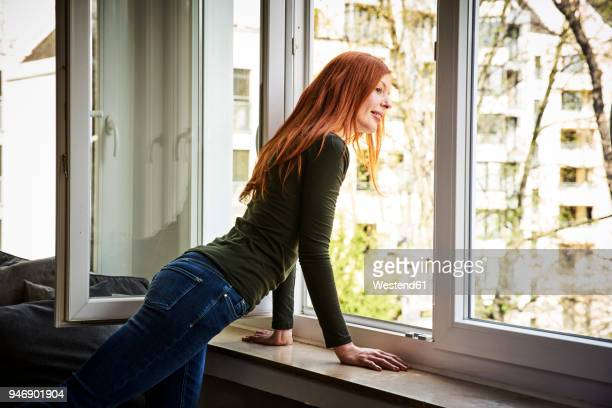 Redheaded woman looking out of window