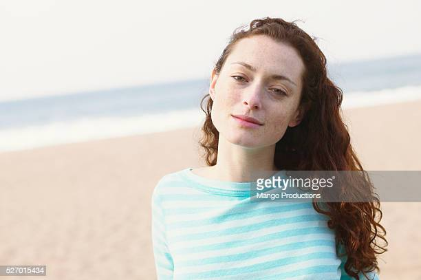 redheaded woman on beach - solo una donna giovane foto e immagini stock