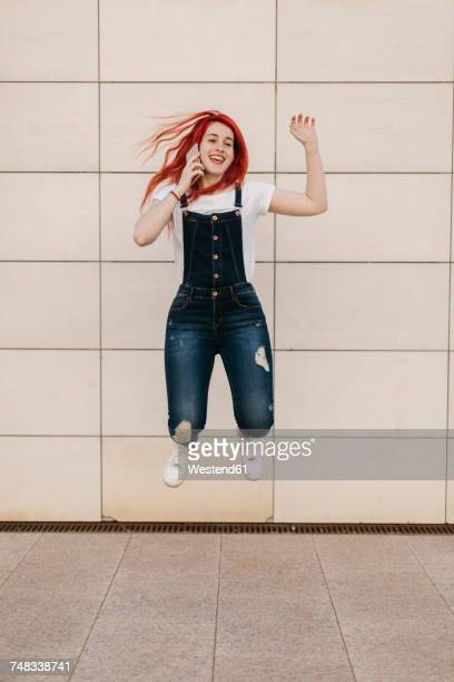 Redheaded woman on the phone jumping in the air
