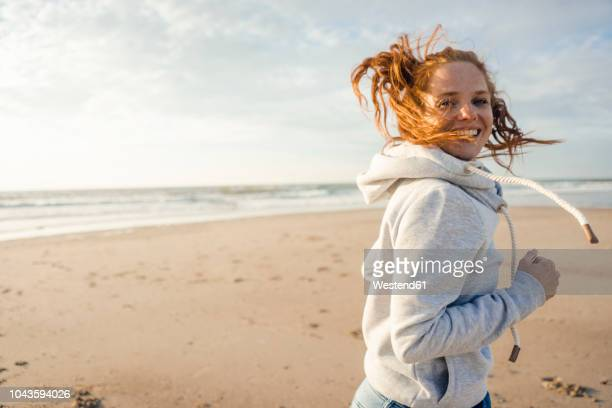 redheaded woman running on the beach, laughing - zorgeloos stockfoto's en -beelden
