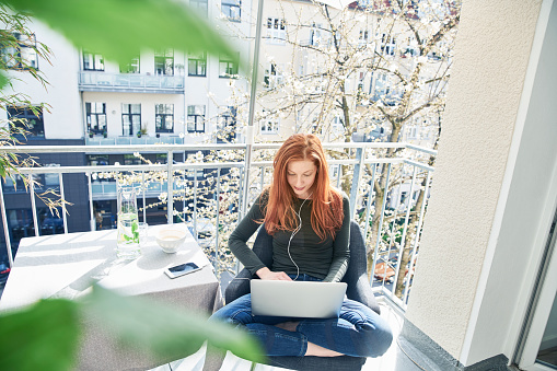 Redheaded woman sitting on balcony using laptop and earphones in spring - gettyimageskorea