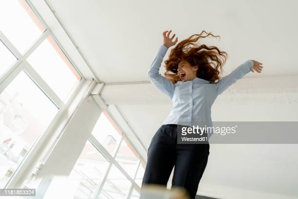 redheaded woman standing on desk in a loft moving and screaming - hysteria stock pictures, royalty-free photos & images