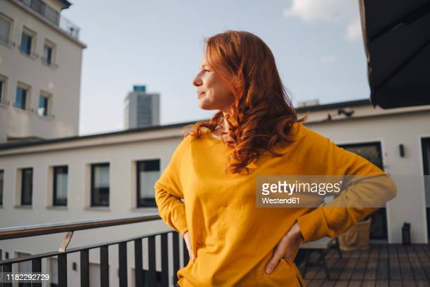 redheaded woman standing on roof terrace - lässige kleidung stock-fotos und bilder