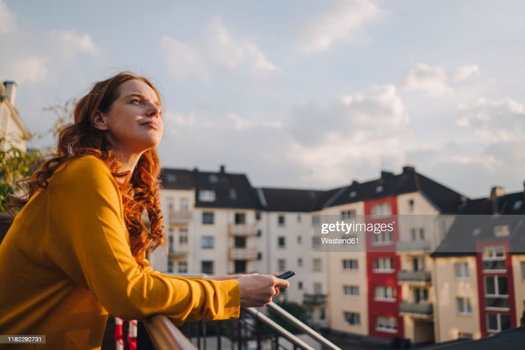 Redheaded woman standing on roof terrace : Stock-Foto