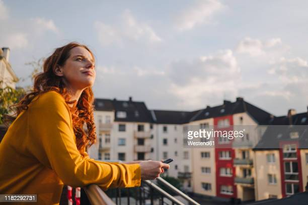 redheaded woman standing on roof terrace - pause machen stock-fotos und bilder