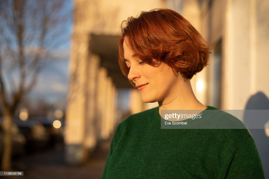 Redheaded woman standing on the street during sunset : Stock-Foto