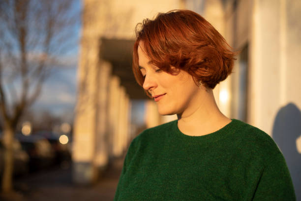 Redheaded woman standing on the street during sunset