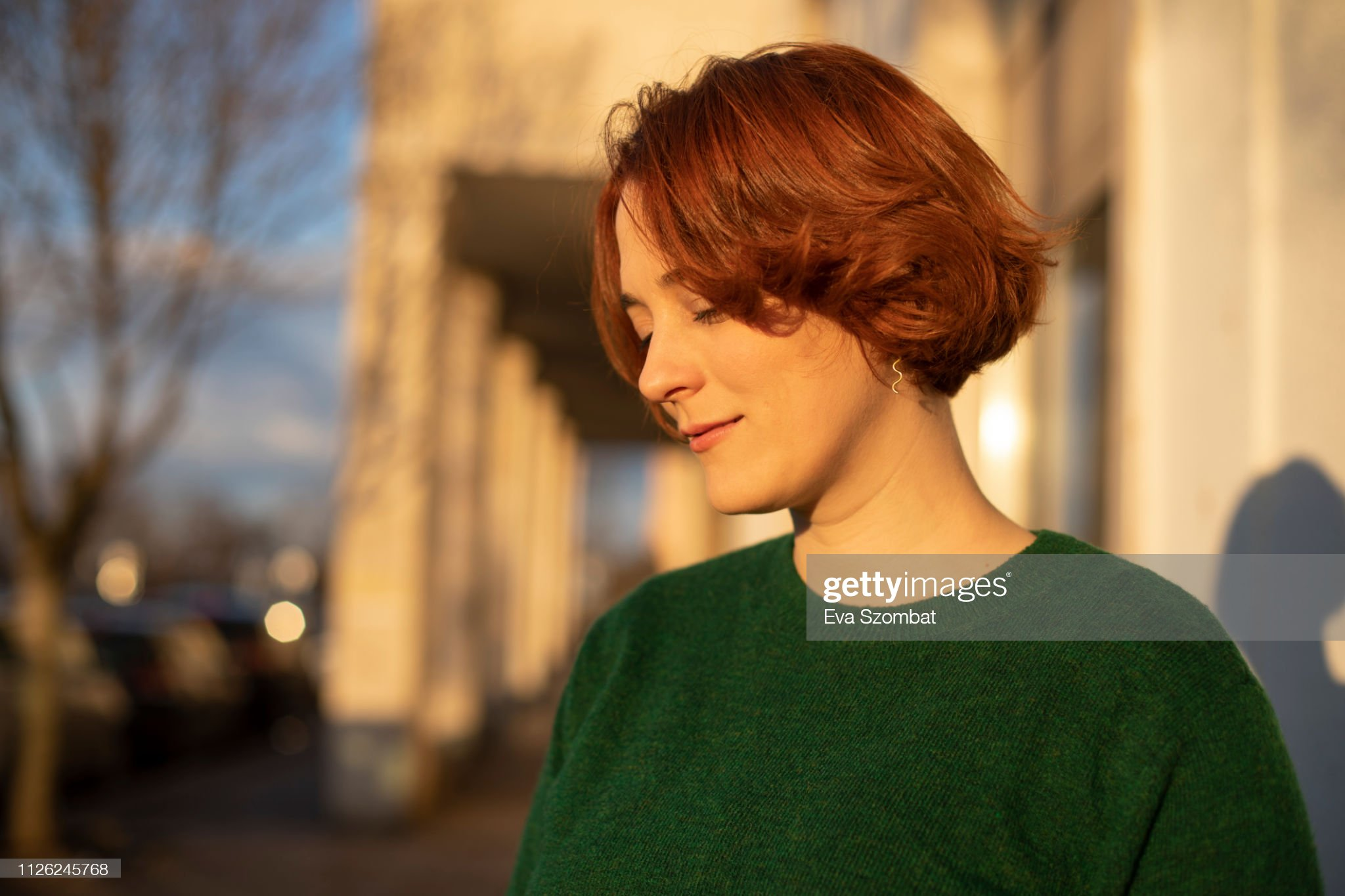 Redheaded woman standing on the street during sunset : Stock Photo