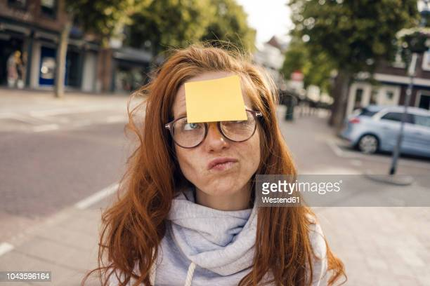 redheaded woman with adhesive note sticking on her forehead - forehead stock pictures, royalty-free photos & images