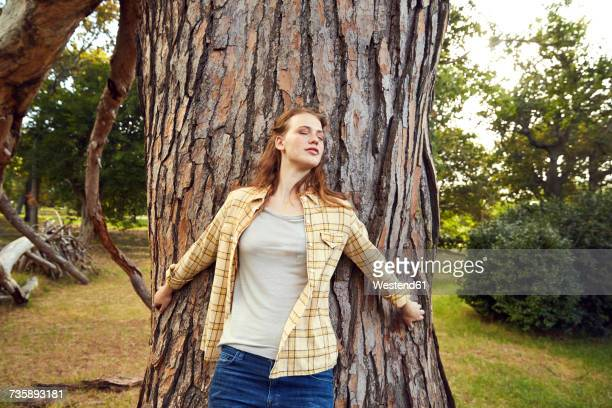 Redheaded young woman leaning against tree trunk with eyes closed