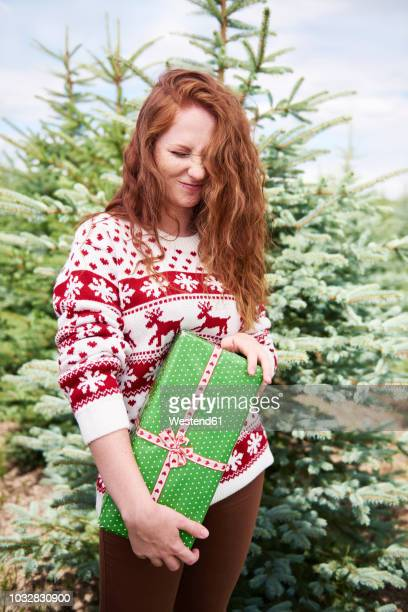 redheaded young woman with christmas present outdoors - wishful skin stock pictures, royalty-free photos & images