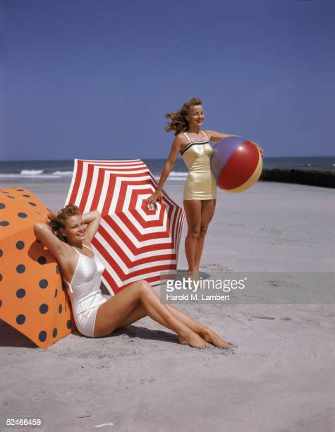 Two women, both redheads, pose on the beach, 1948. One, in a white bathing suit, sits on the sand in front of an orange and black polka-dot umbrella,...
