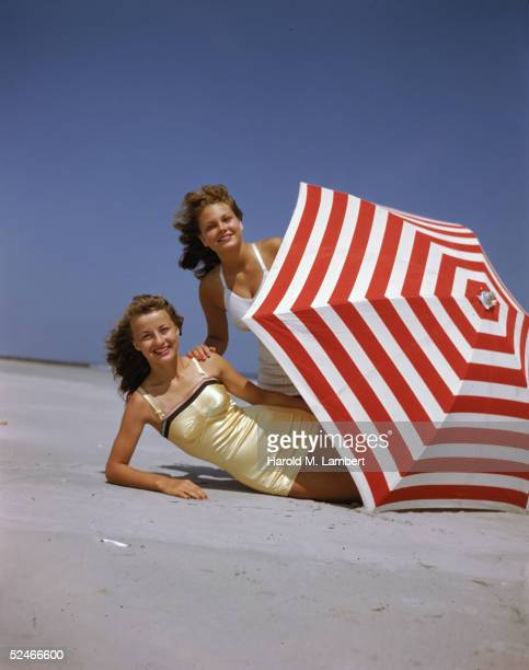 Two women, both redheads, pose behind a red and white umbrella on the beach, 1948. One wears a white bathing suit and the other wears a yellow one.