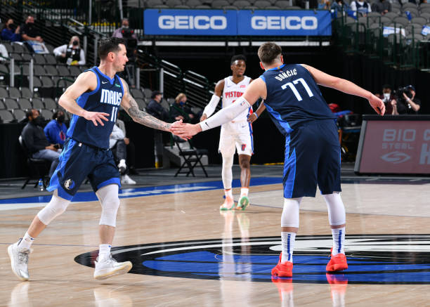 Redick hi-fives Luka Doncic of the Dallas Mavericks during the game against the Detroit Pistons on April 21, 2021 at the American Airlines Center in...