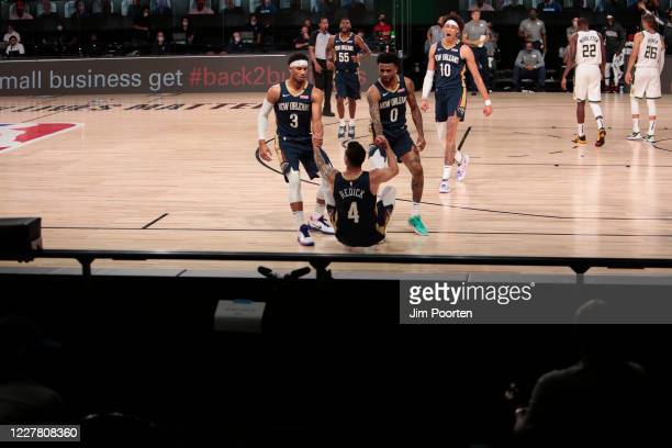 J Redick is helped up by Josh Hart and Nickiel AlexanderWalker of the New Orleans Pelicans against the Milwaukee Bucks as part of the NBA Restart...