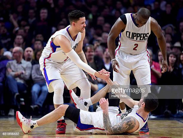 J Redick of the LA Clippers gets help from Austin Rivers after a foul on his three pointer during the first half against the Oklahoma City Thunder at...