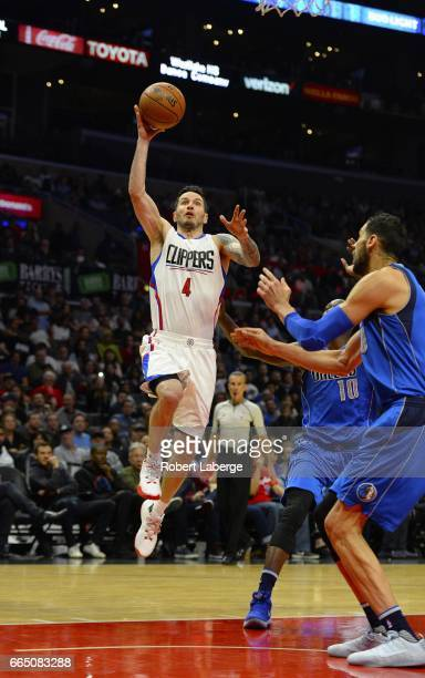 J J Redick of the Los Angeles Clippers attempts a lay up against Dorian FinneySmith and Salah Mejri of the Dallas Mavericks on April 5 2017 at...