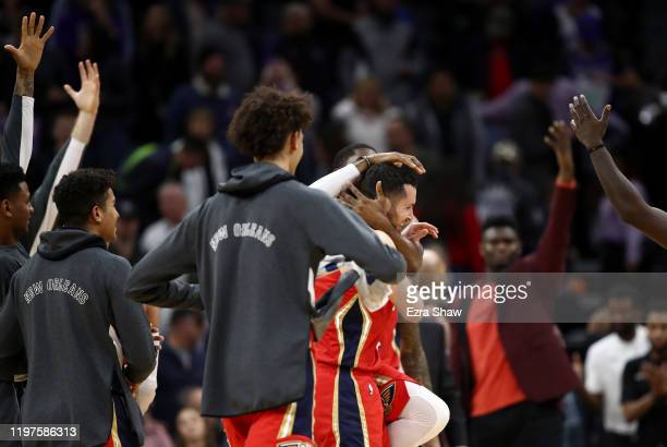 Redick of the New Orleans Pelicans is congratulated by teammates after he made the game winning shot over Richaun Holmes and Cory Joseph of the...