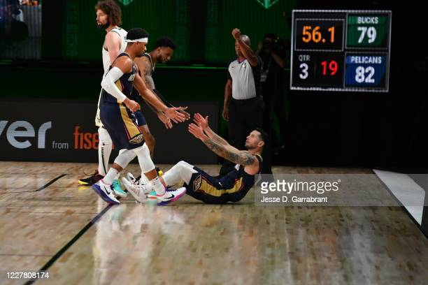 JJ Redick of the New Orleans Pelicans is helped up by his teammates during the game against the Milwaukee Bucks during a scrimmage on July 27 2020 at...