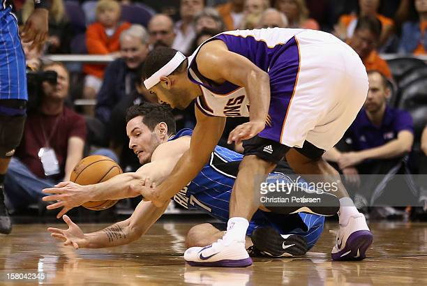 J Redick of the Orlando Magic and Jared Dudley of the Phoenix Suns battle for a loose ball during the NBA game at US Airways Center on December 9...