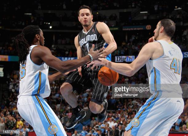 J Redick of the Orlando Magic looses control of the ball against the defense of Kenneth Faried and Kosta Koufos of the Denver Nuggets at Pepsi Center...