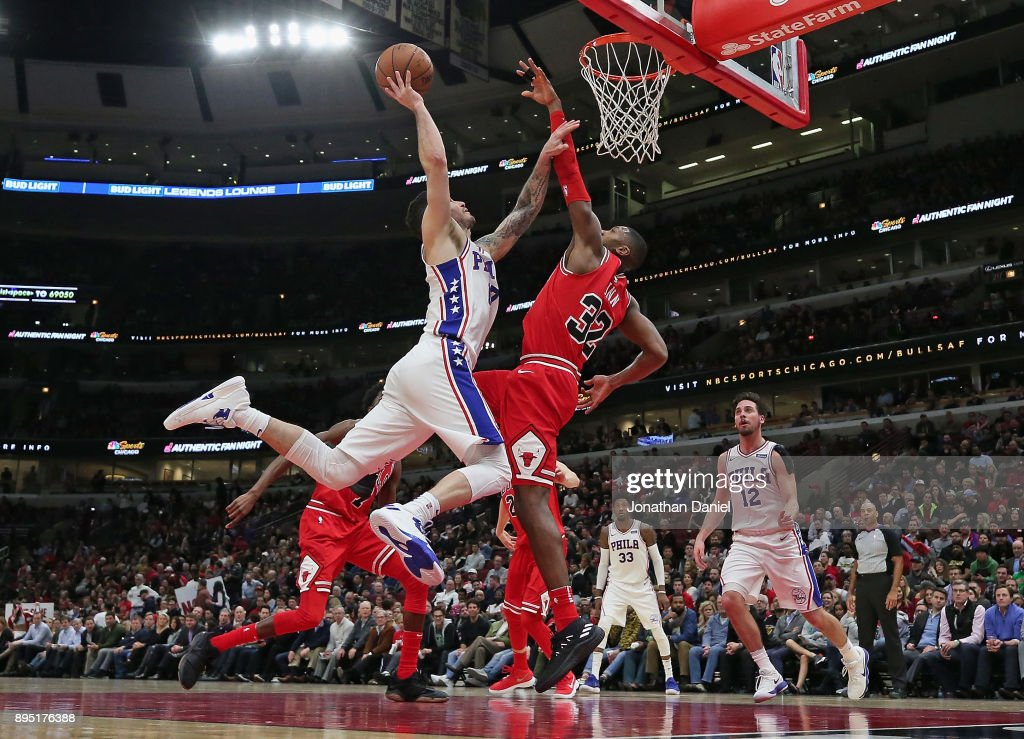 JJ Redick #17 of the Philadelphia 76ers is called for an offensive foul against Kris Dunn #32 of the Chicago Bulls as he puts up a shot at the United Center on December 18, 2017 in Chicago, Illinois. The Bulls defeated the 76ers 117-115.