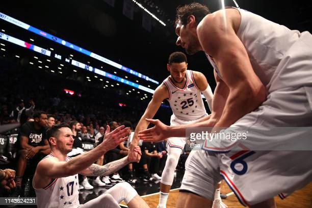 Redick of the Philadelphia 76ers is helped up by teammates Ben Simmons and Boban Marjanovic after a play in the third quarter against the Brooklyn...