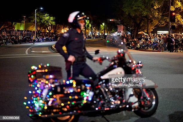 Redlands police officer leading the Christmas parade waits before the start of the parade as the crowd looks on. 2015 Redlands Christmas Parade...